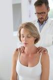 Osteopath fixing woman's posture Stock Photos