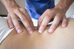 Osteopath hands on patient back Royalty Free Stock Image