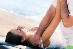 Osteopath manipulating female arm outdoors. Close up of male osteopath doing arm and shoulder treatment on young female athlete outdoors next to sea side royalty free stock image