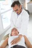 Osteopath manipulating patient's neck. Chiropractor touching woman's head at medical office Stock Image