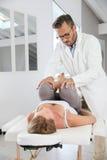 Osteopath manipulating woman's body. Professional physiotherapist stretching woman's leg Stock Photo