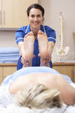 Osteopath treating female client Stock Photography
