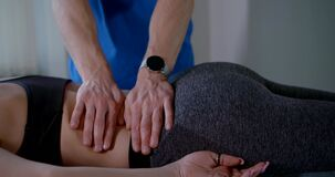 Osteopathic physician is curing spine of young woman, massaging her back