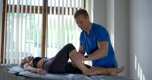 Osteopathic physician is massaging of calf muscle of female patient in modern clinic