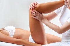 Osteopathic therapist manipulating female knee. Stock Photos
