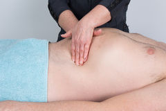 Osteopaths hands doing manipulative visceral massage on man thorax. Stock Photo