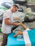 Osteopatterapeuten gör behandlig och massage till foten patienten royaltyfri bild