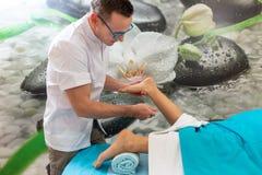 Osteopatterapeuten gör behandlig och massage till foten patienten arkivfoto