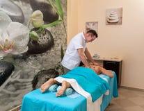 Osteopatterapeuten, gör behandligen och masserar patienten med en skada royaltyfri foto