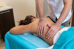 Osteopatterapeuten, gör behandligen och masserar patienten med en skada royaltyfria bilder