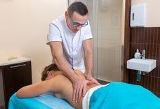 Osteopatterapeuten, gör behandligen och masserar patienten med en skada arkivfoton