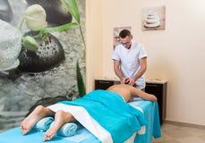 Osteopatterapeuten, gör behandligen och masserar patienten med en skada arkivbild