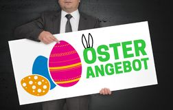 Osterangebot in german Easter offer poster is held by businessman stock photos