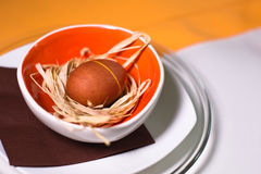 Osterei auf dem Stroh in farbiger Platte und in der Tischdecke lizenzfreie stockbilder