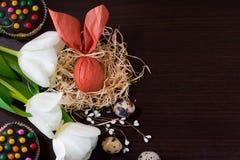 Osterei Browns in Form von Kaninchen im Nest mit Weidenniederlassungen, weißen Tulpen, kleinen Kuchen und Wachteleiern Stockbilder
