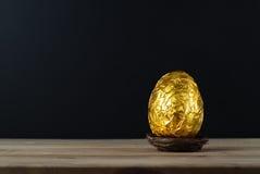 Osterei eingewickelt im Goldfolien-Papier mit schwarzem Hintergrund Lizenzfreie Stockfotografie