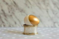 Osterei, gemaltes Gold und weiß, auf silbernem Behälter Stockbild