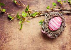 Osterei im Nest auf hölzernem Hintergrund Lizenzfreie Stockfotos