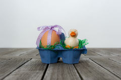 Osterei mit einem Band und eine kleine Ente in einem Karton Stockbilder