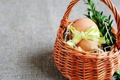 Osterei mit gelbem Band in einem Korb Stockbild