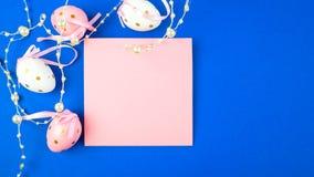 Osterei verziert mit Perlen auf einem blauen Hintergrund und einem rosa Blatt Papier stockfotos