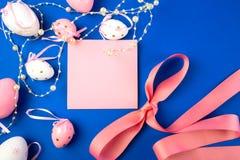 Osterei verziert mit Perlen auf einem blauen Hintergrund und einem rosa Blatt Papier lizenzfreies stockfoto