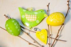 Ostereidekorationen mit Vogel auf Holztisch Stockfoto