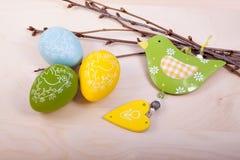 Ostereidekorationen mit Vogel auf Holztisch Stockfotografie