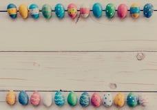 Ostereier auf hölzernem Hintergrund Bunte Ostereier und Hand Lizenzfreie Stockfotos