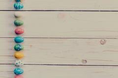 Ostereier auf hölzernem Hintergrund Bunte Ostereier und Hand Stockbilder