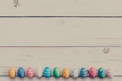 Ostereier auf hölzernem Hintergrund Bunte Ostereier und Hand Stockfotografie
