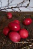 Ostereier der roten Farbe auf einem hölzernen Hintergrund, zusammen mit Herbst verzweigt sich Stockfotografie