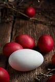 Ostereier der roten Farbe auf einem hölzernen Hintergrund, zusammen mit Herbst verzweigt sich Lizenzfreies Stockbild
