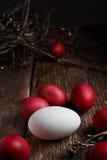 Ostereier der roten Farbe auf einem hölzernen Hintergrund, zusammen mit Herbst verzweigt sich Lizenzfreie Stockfotos