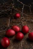 Ostereier der roten Farbe auf einem hölzernen Hintergrund, zusammen mit Herbst verzweigt sich Lizenzfreies Stockfoto
