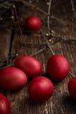 Ostereier der roten Farbe auf einem hölzernen Hintergrund, zusammen mit Herbst verzweigt sich Lizenzfreie Stockfotografie