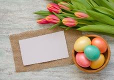 Ostereier in der Schüssel und in den Tulpen mit einer weißen Karte auf dem hölzernen Hintergrund der Weinlese Stockfotos