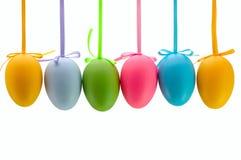 Ostereier, die an den Farbbändern hängen. Getrennt. Stockfotos