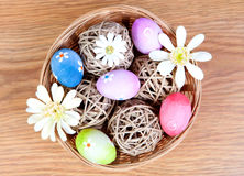 Ostereier, die mit Gänseblümchen verziert wurden, verstauten herein einen Korb Stockfotografie