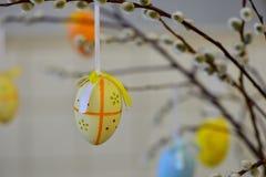 Ostereier, die von den Weidenniederlassungen hängen Gemalte Eier und Blumen Stockbild