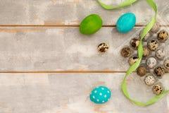 Ostereier, ein helles Band und Wachteleier auf der hellen Holzoberfläche, Nahaufnahme Platz, zum Ihres Textes einzufügen Fröhlich Stockbilder