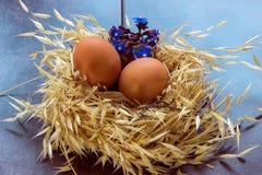 Ostereier in einem Nest mit Blumen Stockfoto