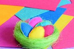 Ostereier in einem Nestdekor Filz-Ostereier stellten in ein grünes Sisalsnest auf mehrfarbigen Filzblättern ein Heller paschal Hi Stockfotografie