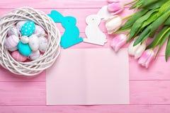 Ostereier in einem Weidenkorb und in einem Blumenstrauß von Tulpen auf einem rosa Hintergrund Feiertagsgrußkarte für Ostern! lizenzfreie stockfotografie