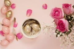 Ostereier in einer Schüssel Rosa und Gold-Ostereier Pastell-Ostern-Konzept mit Eiern, Blumen und Federn Lizenzfreie Stockfotos