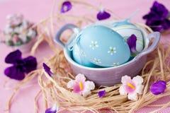 Ostereier in einer Schüssel und in purpurroten Gartennelken Lizenzfreie Stockfotos