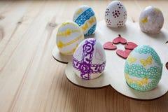 Ostereier gemalt auf einem hölzernen Stand, auf einem hölzernen Hintergrund Stockfoto