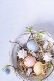 Ostereier gemalt mit empfindlicher Pastellfarbe in gesponnen ringsum Korb, weißen Hintergrund Frühlingsfeiertag Beschneidungspfad Stockfotografie