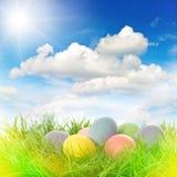 Ostereier im Gras Sonniger blauer Himmel mit Sonnenstrahlen und heller Weide Lizenzfreies Stockfoto