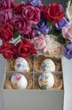 Ostereier im Kasten mit gefälschten Rosen Lizenzfreies Stockbild